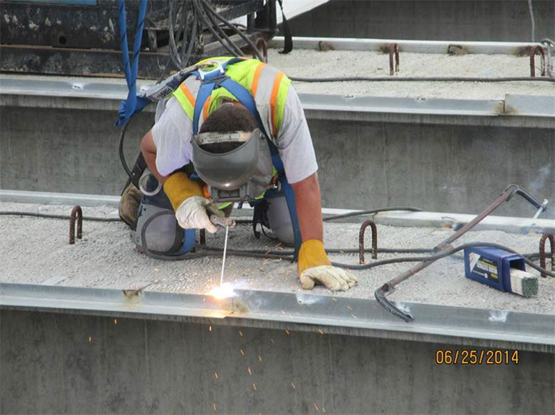 Welding angle clips to girders to support the steel deck pans