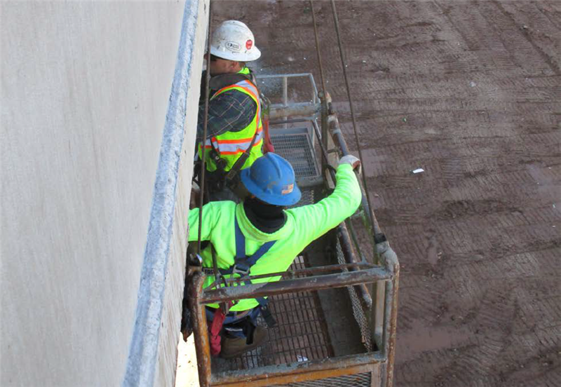 Working over the side of the bridge.