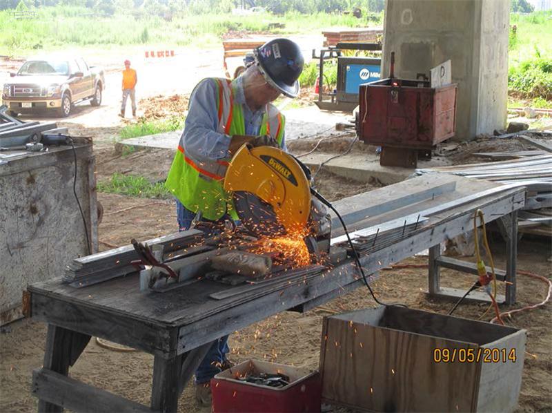 Welder cutting straps for bridge deck