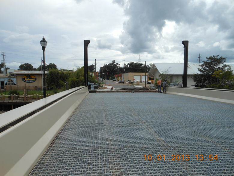 All structural metal has been installed, contractor is beginning to check deflections and balance bridge. Traffic barrier columns and walkway luminaires in background